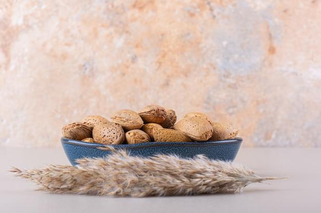 흰색 바탕에 벗겨진 된 유기농 아몬드의 어두운 그릇. 고품질 사진