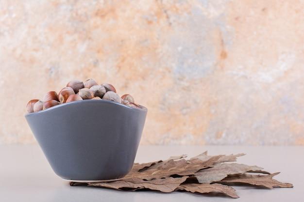 흰색 배경에 껍질을 벗긴 유기농 헤이즐넛과 마른 잎의 어두운 그릇. 고품질 사진 무료 사진