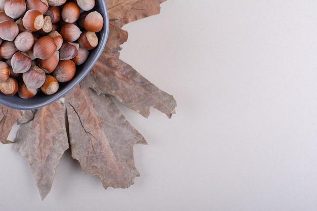 흰색 배경에 껍질을 벗긴 유기농 헤이즐넛과 마른 잎의 어두운 그릇. 고품질 사진