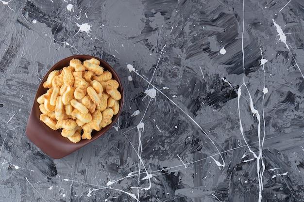 大理石のテーブルの上のおいしい塩味のクラッカーの暗いボウル。