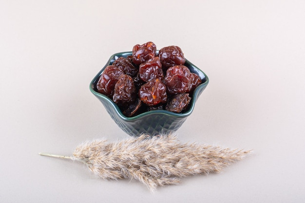 Dark bowl of organic dry dates on white table. high quality photo