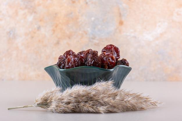 Dark bowl of organic dry dates on white table.