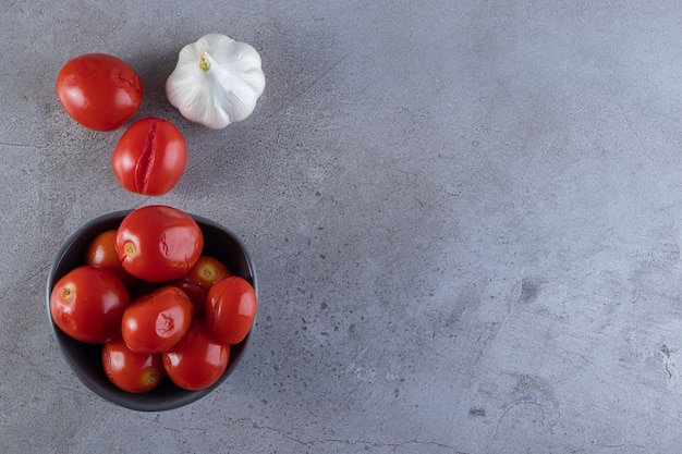 Dark bowl of pickled tomatoes placed on stone table.