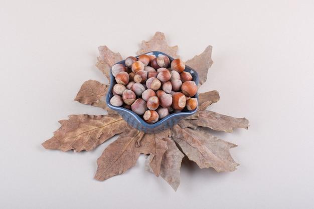 Ciotola scura di nocciole naturali sgusciate e foglie secche su sfondo bianco. foto di alta qualità
