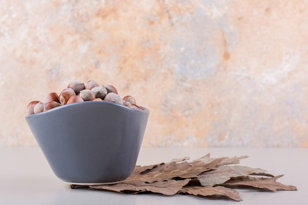 Dark bowl of shelled organic hazelnuts and dry leaves on white background. high quality photo
