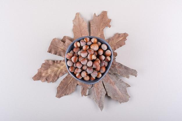 Ciotola scura di nocciole organiche sgusciate e foglie secche su sfondo bianco. foto di alta qualità
