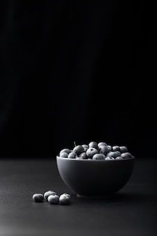 Dark bowl with cranberries on a dark background