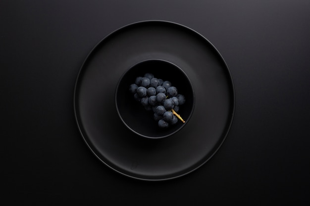 Dark bowl with gapes on a dark background