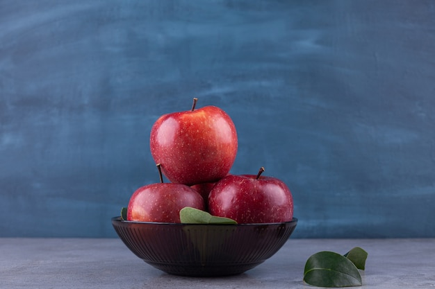 Темная миска с блестящими красными яблоками на каменной поверхности.
