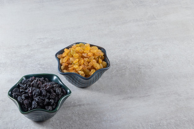 Ciotole scure con uvetta dorata e nera essiccata su fondo di pietra.