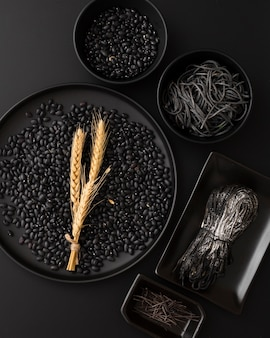Dark bowls with pasta and beans on a black background