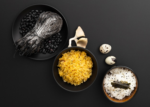Dark bowls with pasta and rice on a dark background