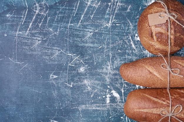 Булочки темного хлеба на деревянной доске.