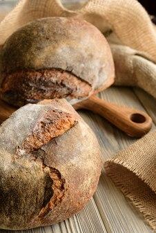 Крупный план темного хлеба с мешковиной и разделочной доской.