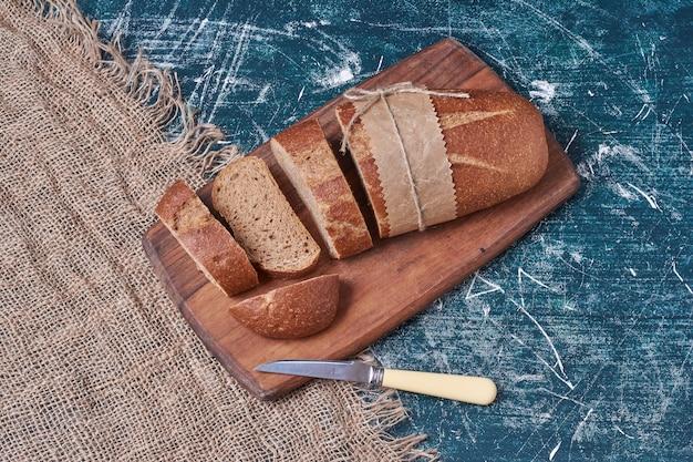 나무 절단 보드에 어두운 빵입니다.