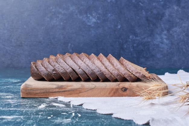 青いテーブルの上の暗いパンのスライス。