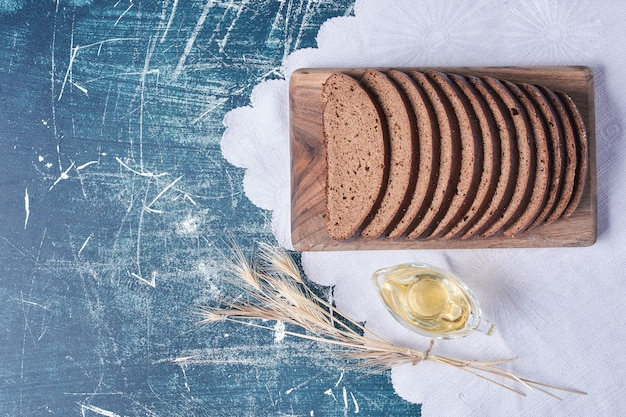 青いテーブルの上の白いタオルの上の暗いパンのスライス。