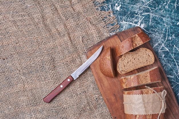 Ломтики темного хлеба на деревянной доске.