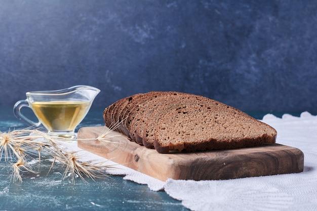 Fette di pane scuro con olio sulla tavola blu.
