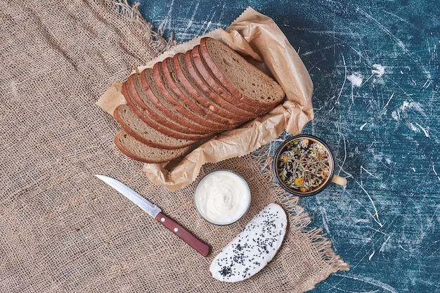 Ломтики темного хлеба со сметаной на синем.