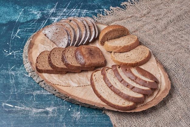 Fette di pane scuro sulla tavola di legno sul tavolo blu.