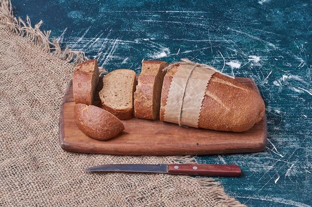 Fette di pane scuro su tavola di legno.