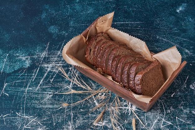 Fette di pane scuro in un vassoio di legno.