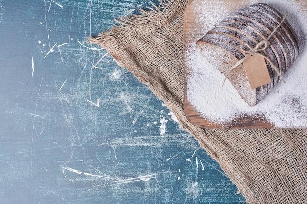 青いテーブル、上面図に素朴な糸で結ばれた暗いパン。