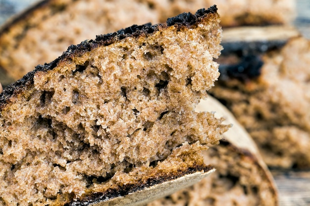Dark bread with a crisp crust on a wooden table, bread broken into a large number of pieces, soft and delicious flesh