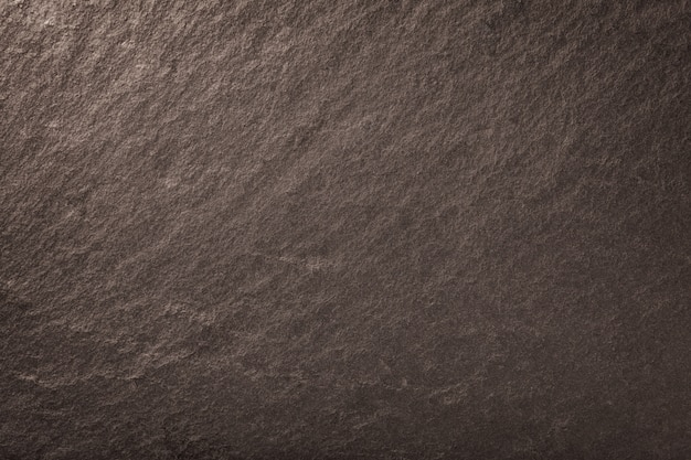 Dark bronze background of natural slate. texture of brown stone closeup. graphite backdrop macro
