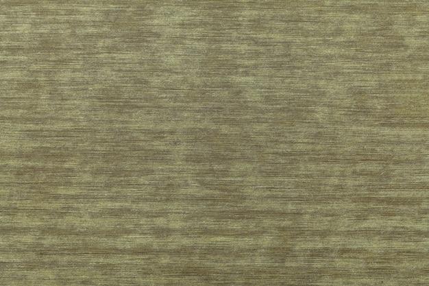 ダークブラウンとグリーンのぼろぼろのヴィンテージラミネート。木製のテクスチャの背景、クローズアップ。オリーブの節くれだったパターンと古い装飾的な木の背景の構造。装飾の壁紙。