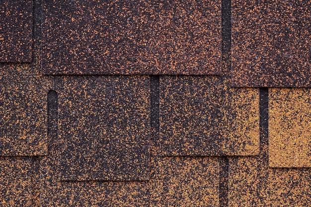 屋根瓦の暗褐色と黄色の表面。