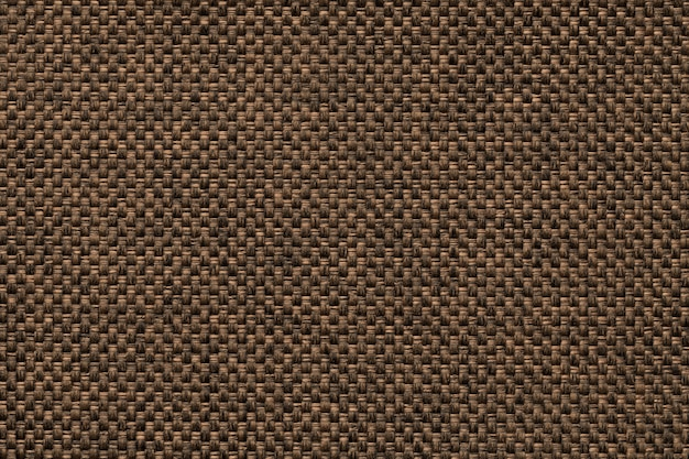 Dark brown background of dense woven bagging fabric, closeup. structure of the textile macro.