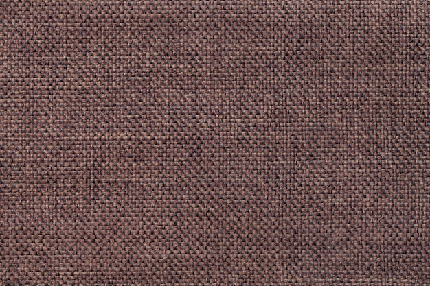 Dark brown background of dense woven bagging fabric, closeup. structure of the umber cloth with natural texture. cloth backdrop. Premium Photo