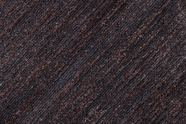 Dark brown background of a knitted textile material. fabric with a striped texture closeup.