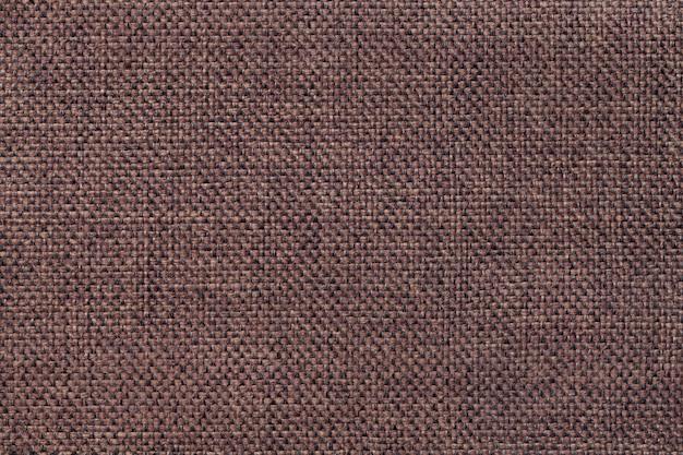 Темно-коричневый фон плотной тканой мешковиной ткани, крупным планом. структура умбры с натуральной текстурой. тканевый фон.