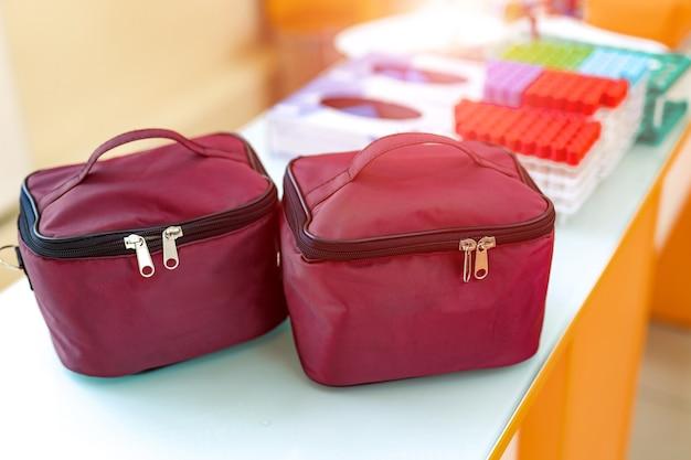 Тканевые косметички темно-коричневого цвета на молнии. две сумки для косметики на столе с размытым фоном.