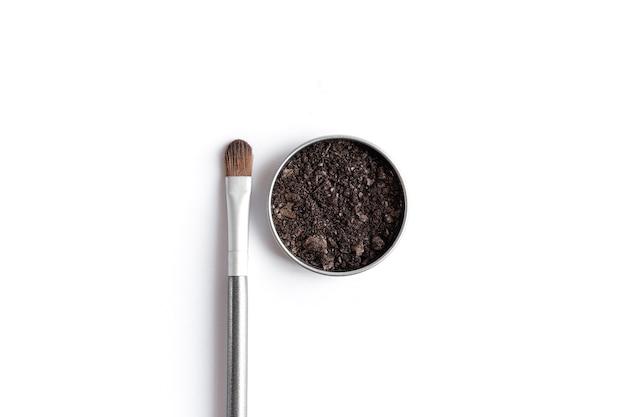 Темно-коричневые тени для лица в контейнере и тени для век или кисть для макияжа. макияж концепция плоской планировки