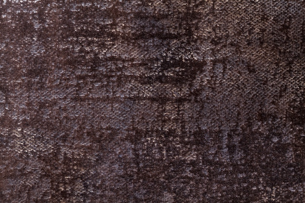 Dark brown fluffy background of soft, fleecy cloth. texture of black textile backdrop with shiny pattern.