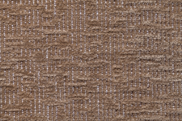 Dark brown fluffy background of soft, fleecy cloth. texture of plush furry textile, closeup.