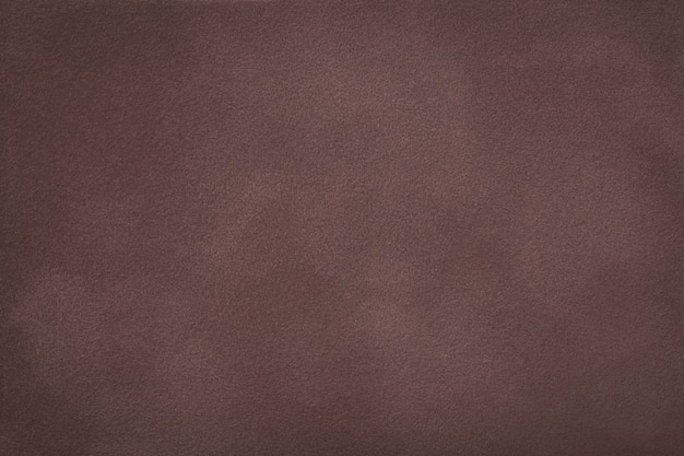 Dark brown matt suede fabric closeup. velvet texture.