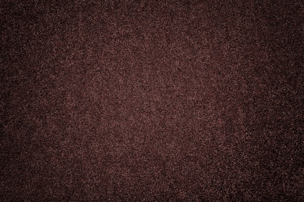 Dark brown matte background of suede fabric. velvet texture of umber woolen felt with vignette.