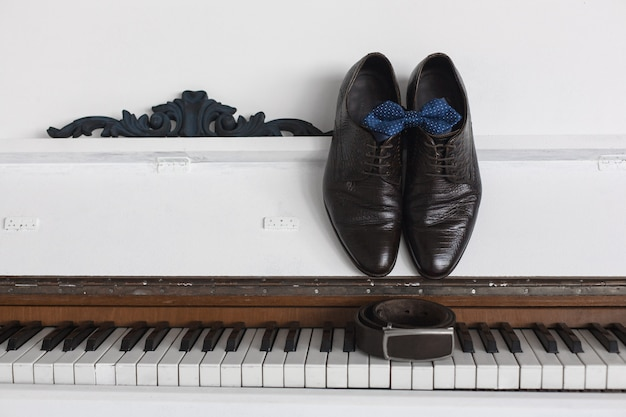 Dark brown men's shoes and strap on a white background
