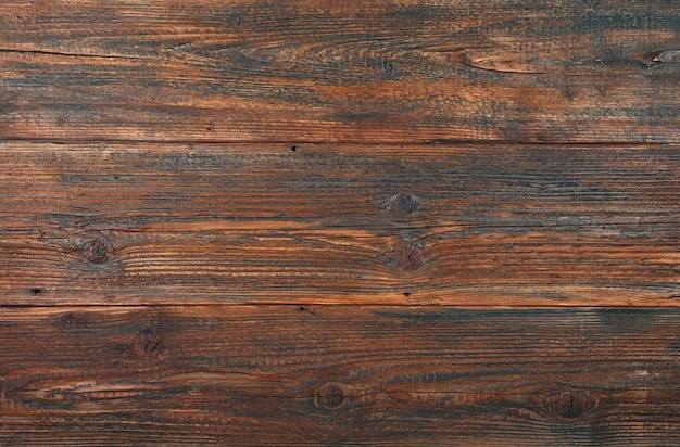 Dark brown old vintage knotty wooden wide planks background