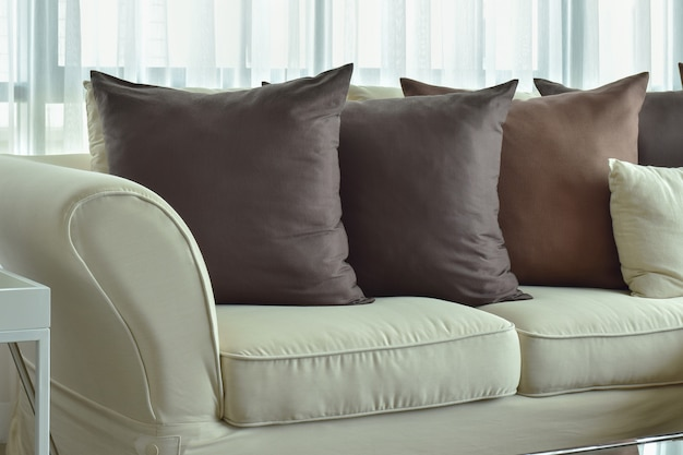 Dark brown pillows setting on beige color sofa