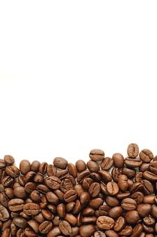 コピースペースで白い背景に分離されたダークブラウンの焙煎コーヒー豆
