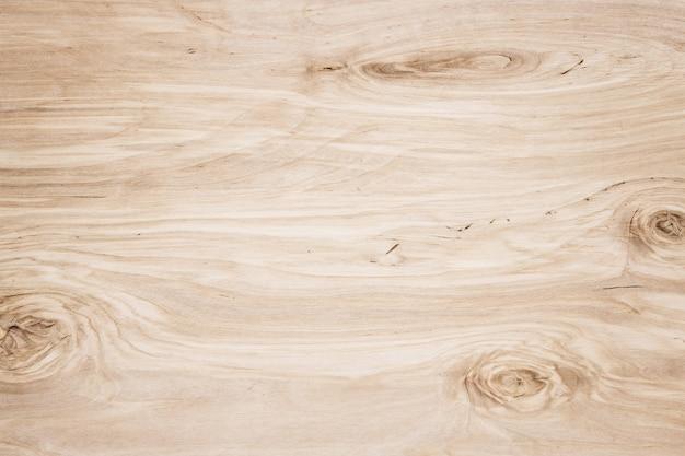 ダークブラウンの傷のある木製のまな板。木目調の壁