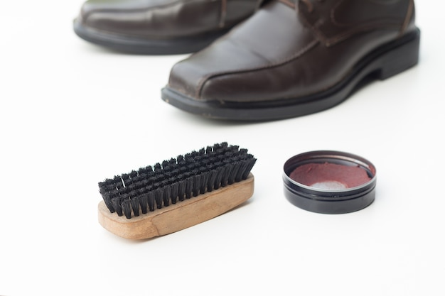 Dark brown shoe with shoe polish and brush shoe