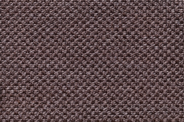 Dark brown textile background with checkered patterno.