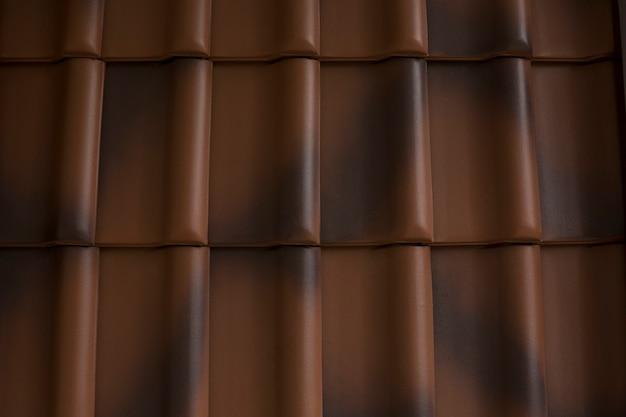 屋根の上の帯状疱疹の暗褐色のタイル。クローズアップショット